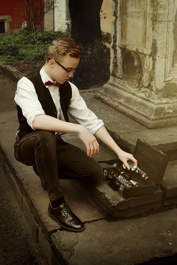 Hombre elegante del inconformista que sostiene el clarinete y que lo pone en el caso fotografía de archivo
