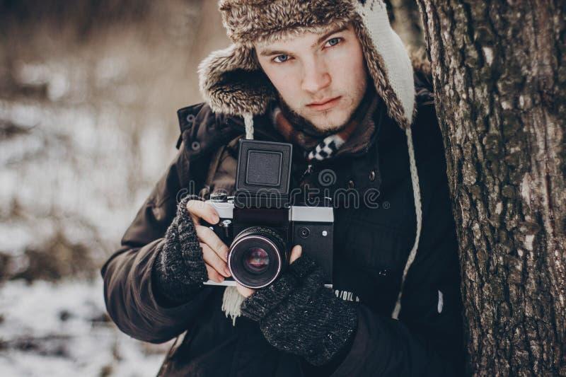 Hombre elegante del viajero del inconformista con la cámara vieja de la foto que explora adentro imagen de archivo libre de regalías