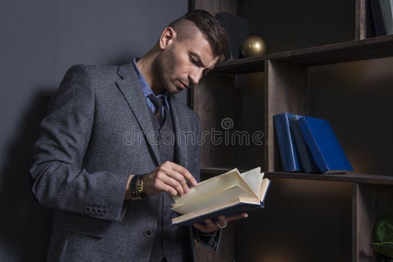 Hombre elegante en traje de negocios con el libro Retrato del hombre elegante hermoso en biblioteca El abogado lee el libro fotografía de archivo