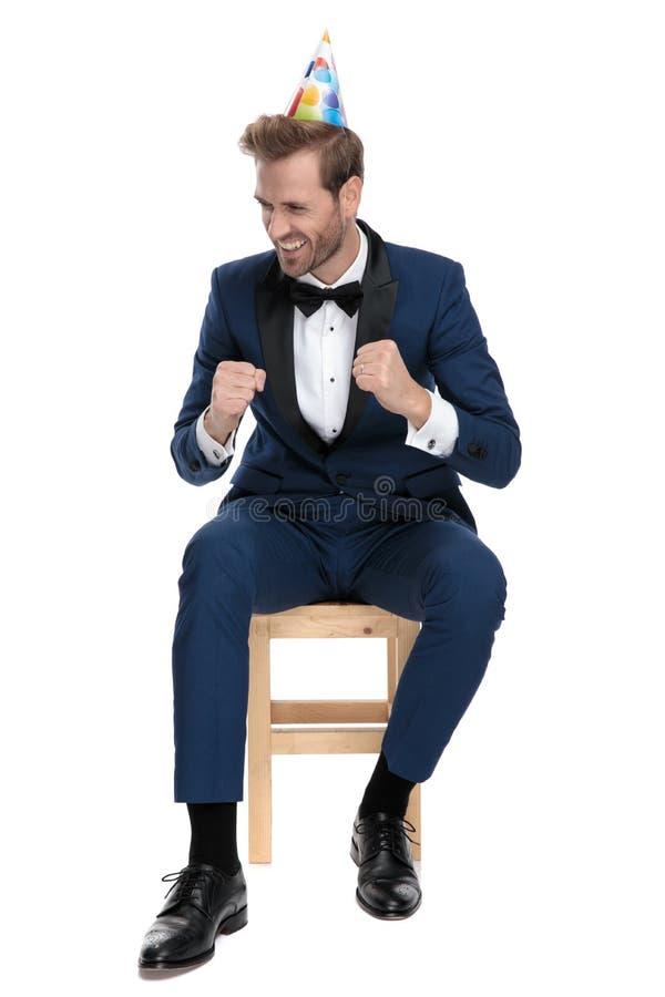 Hombre elegante feliz asentado que celebra la fiesta de cumpleaños imagen de archivo libre de regalías