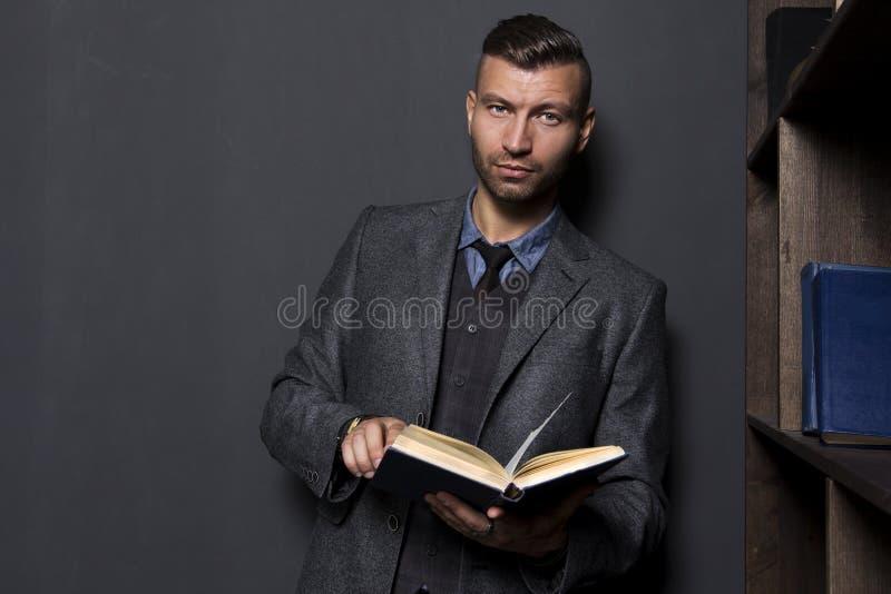 Hombre elegante hermoso elegante en traje de negocios con el libro fotos de archivo libres de regalías