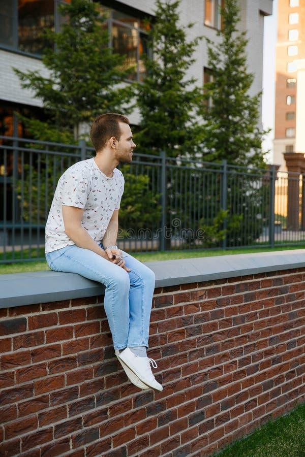 Hombre elegante hermoso joven con las cerdas que se sientan en una cerca del ladrillo cerca del edificio en una tarde del verano fotos de archivo libres de regalías