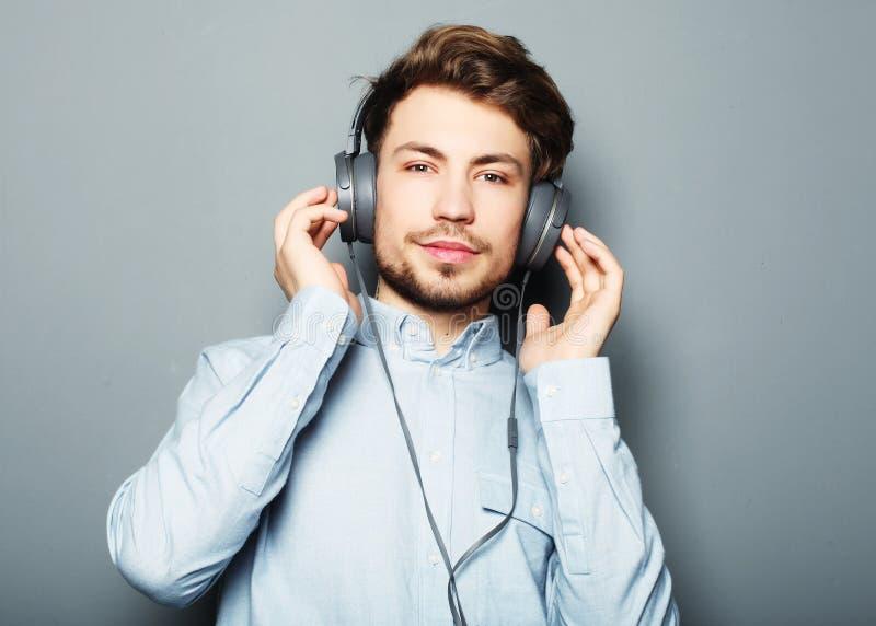 Hombre elegante joven feliz que ajusta su wh sonriente del anuncio de los auriculares foto de archivo