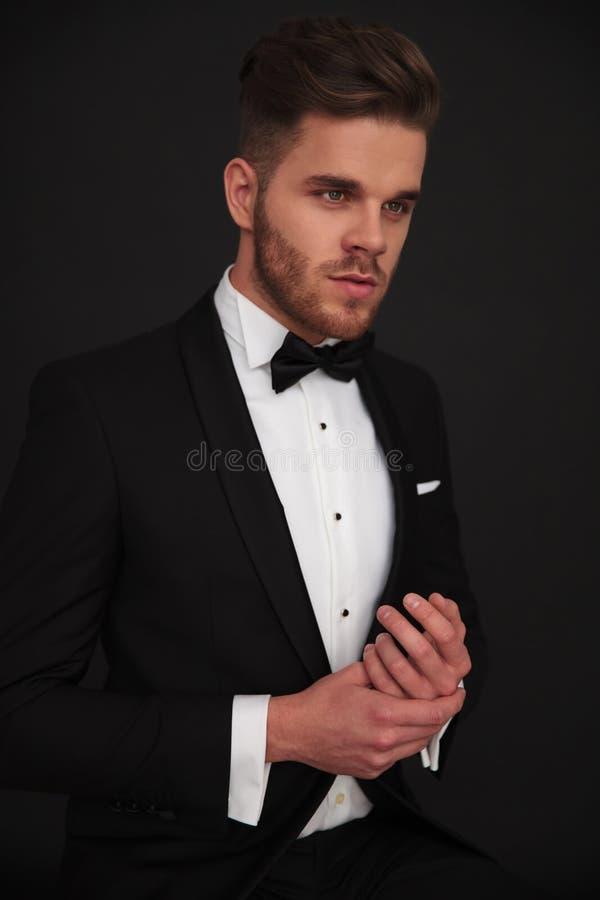 Hombre elegante joven que lleva a cabo sus manos y que mira lejos imagen de archivo