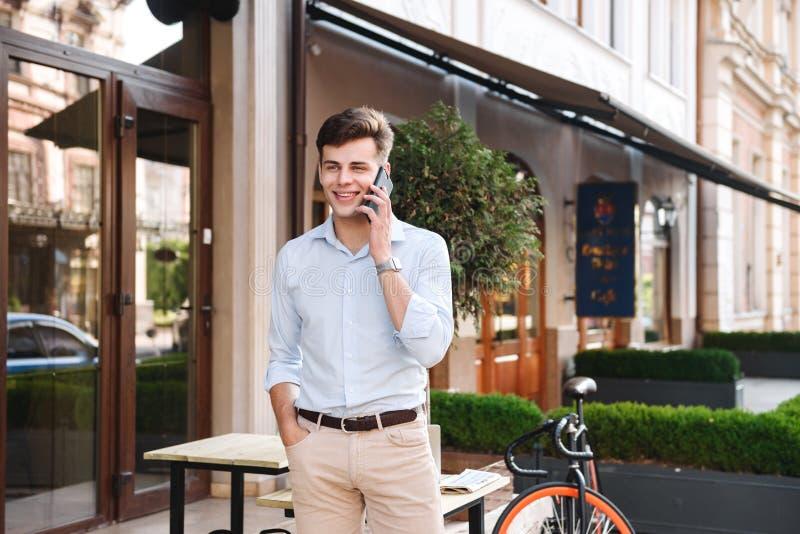 Hombre elegante joven sonriente en camisa que habla en el teléfono móvil foto de archivo libre de regalías