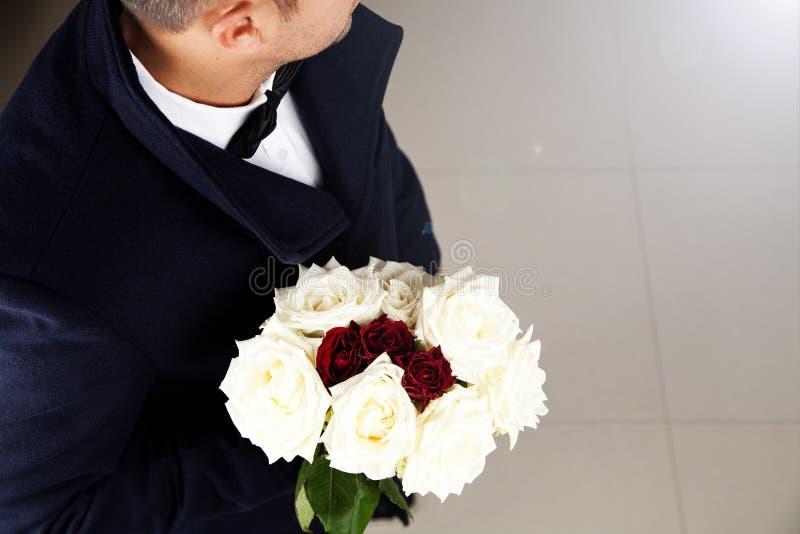 Hombre elegante que espera alguien con el ramo hermoso de rosas imagen de archivo