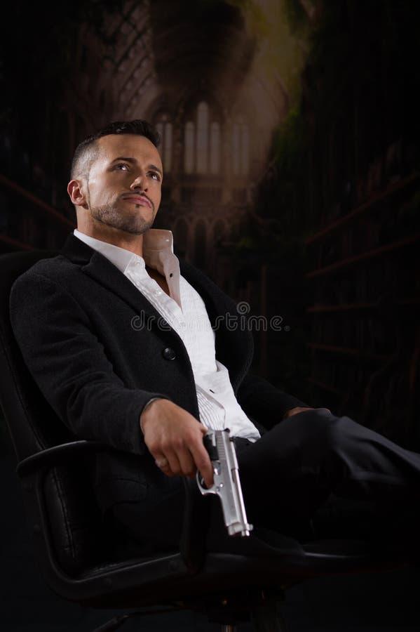 Hombre elegante que se sienta en una silla que aplaza el arma imagenes de archivo