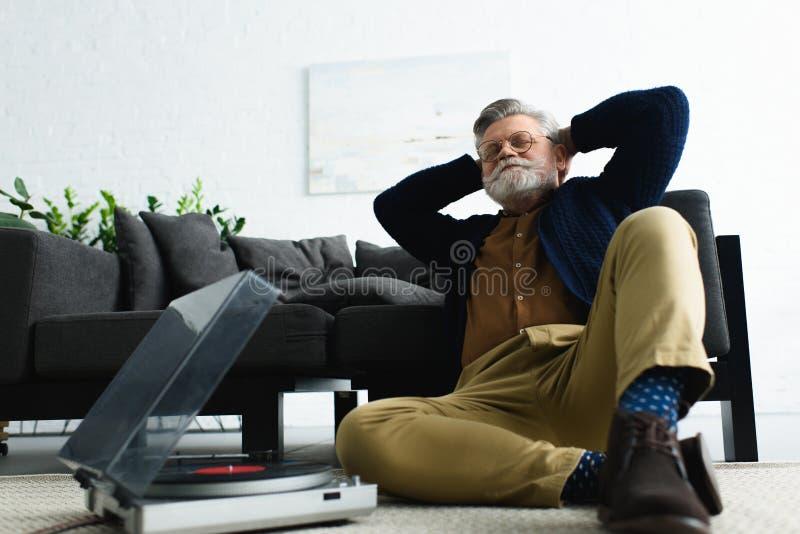 hombre elegante relajado en las lentes que se sientan con las manos detrás de la cabeza y de la música que escucha con el jugador foto de archivo libre de regalías