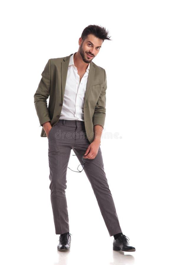 Hombre elegante sonriente que parece relajado mientras que sostiene los vidrios fotos de archivo
