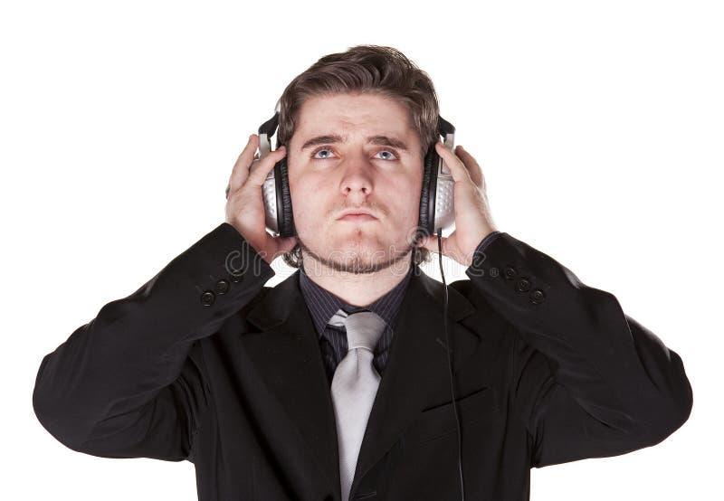 Hombre elegante vestido que escucha en los auriculares imagenes de archivo