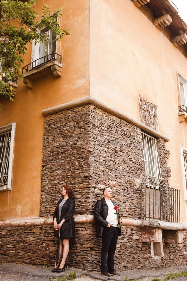 Hombre elegante y situaci?n de mediana edad de la mujer cerca de la pared de piedra de la casa en el verano Bast?n del paraguas y fotos de archivo