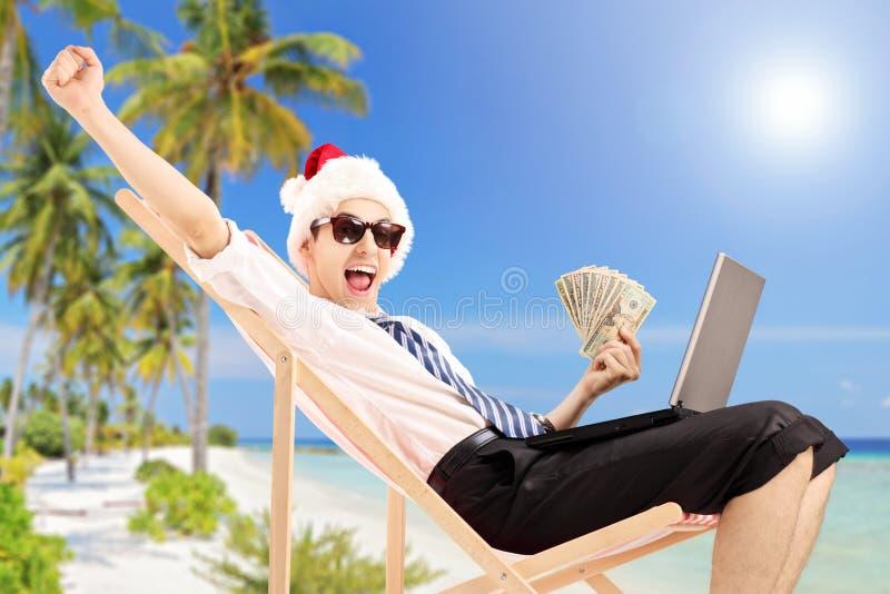 Hombre emocionado con el sombrero de santa en una silla de playa que sostiene billetes de banco imagen de archivo libre de regalías