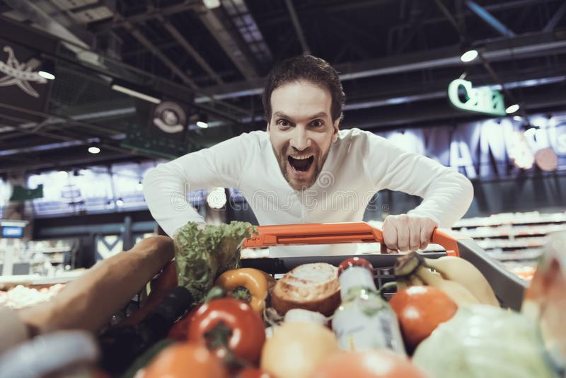 Hombre emocionado con la carretilla de las compras en supermercado foto de archivo
