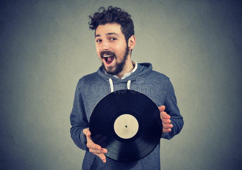 Hombre emocionado del inconformista con el disco de vinilo que mira la cámara imágenes de archivo libres de regalías