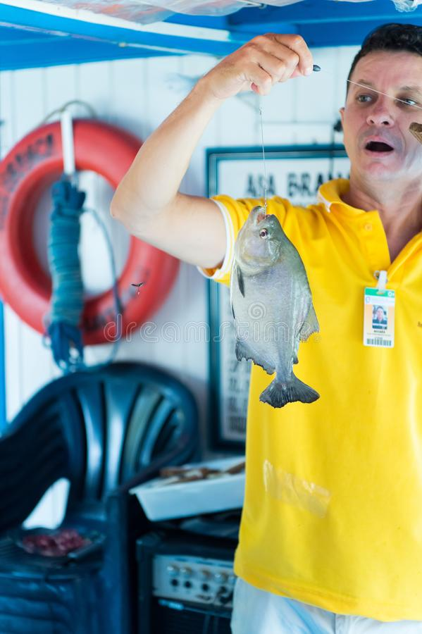 Hombre emocionado en la camiseta amarilla que sostiene pescados en línea fotografía de archivo libre de regalías