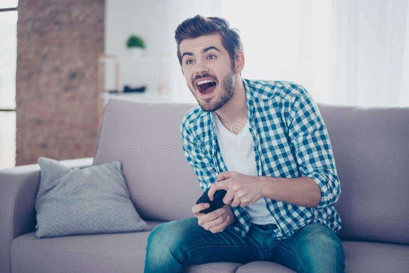 Hombre emocionado feliz joven que se sienta en el sofá que sostiene el joypad y el playi fotografía de archivo