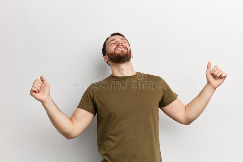 Hombre emocionado joven con los brazos aumentados que miran para arriba imagen de archivo libre de regalías