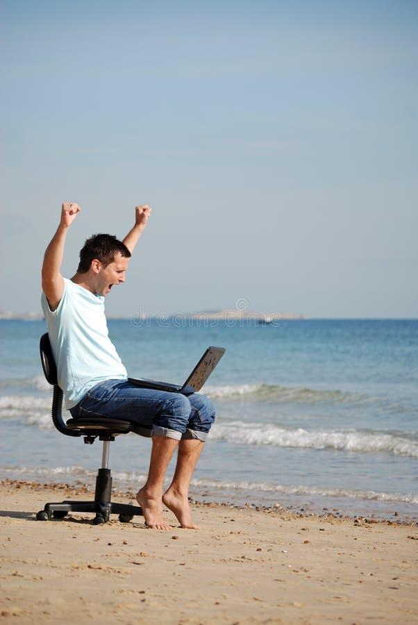 Hombre emocionado que anima en la computadora portátil fotos de archivo libres de regalías