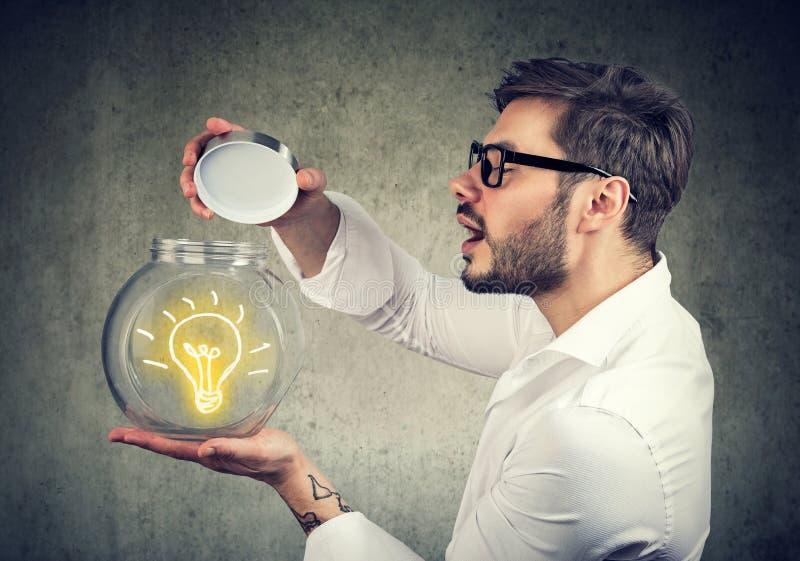 Hombre emocionado que celebra la apertura de un tarro de cristal con el lighbulb brillante de la idea dentro fotos de archivo libres de regalías