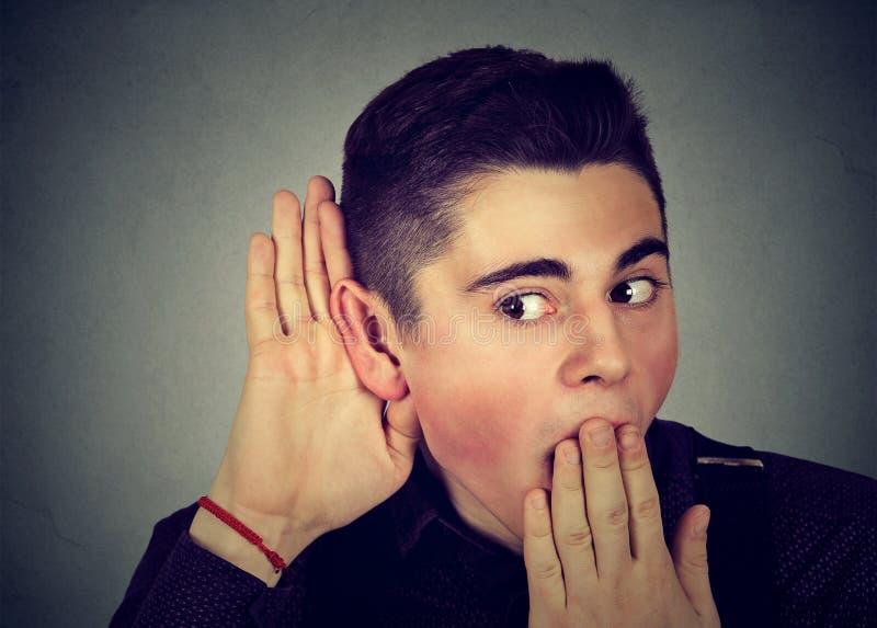 Hombre emocionado que escucha las rumores foto de archivo