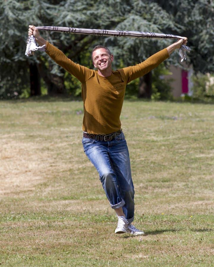 Hombre emocionado 40s que expresa euforia y la libertad en parque imagen de archivo libre de regalías