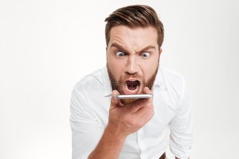 Hombre emocional barbudo joven enojado de griterío que habla por el teléfono fotos de archivo
