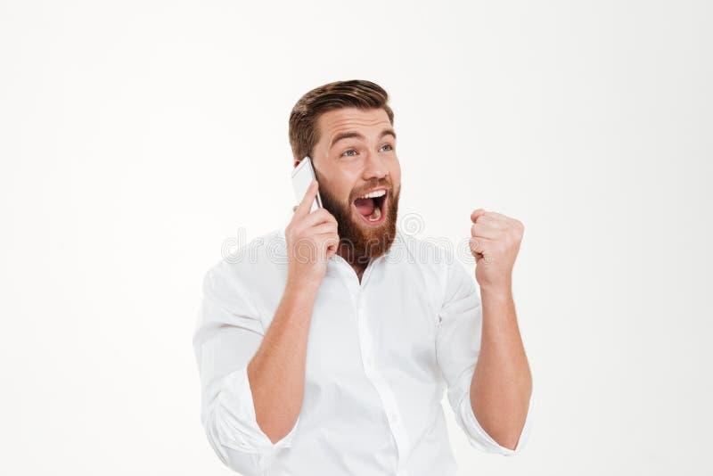 Hombre emocional barbudo joven feliz que habla por el teléfono imagenes de archivo