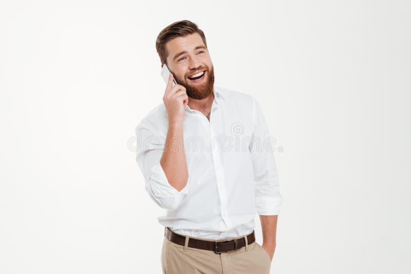 Hombre emocional barbudo joven feliz que habla por el teléfono imagen de archivo libre de regalías