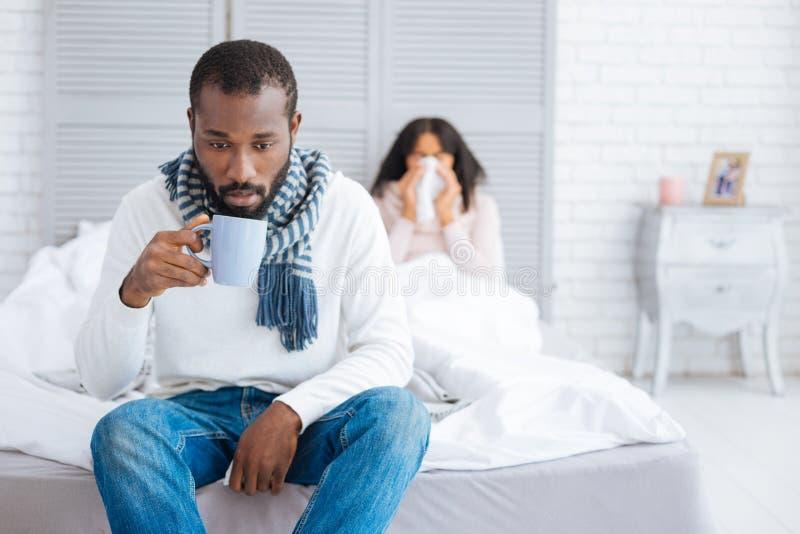 Hombre emocional cansado que se sienta con una taza cerca de su esposa foto de archivo