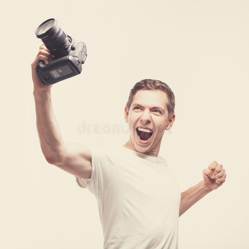 Hombre emocional con la cámara aislada en fondo ligero Cámara digital de la tenencia del hombre joven con la victoria que grita F fotos de archivo