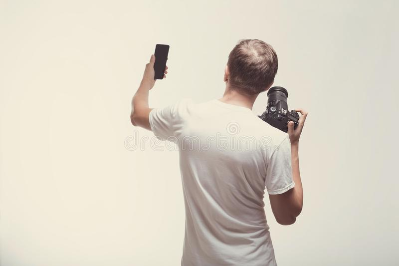 Hombre emocional con la cámara aislada en fondo ligero Cámara digital y smartphone del control del hombre joven Forma de vida, vi foto de archivo