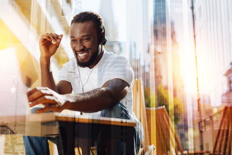 Hombre emocional que ríe mientras que teniendo una conversación video en un café imagen de archivo