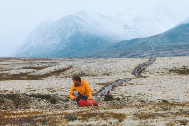 Hombre empaquetando mochila para viajar engranajes de senderismo en las montañas foto de archivo libre de regalías