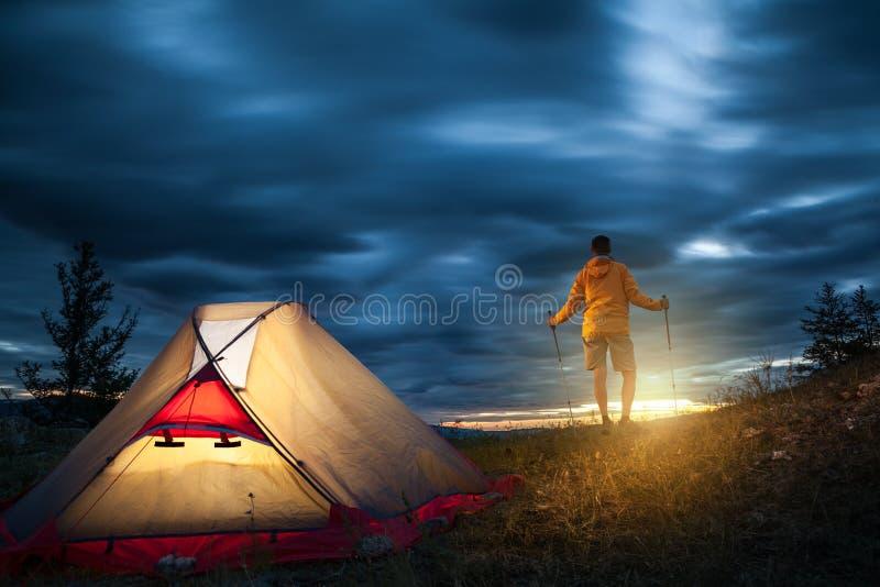 Hombre en acampar en la salida del sol fotografía de archivo