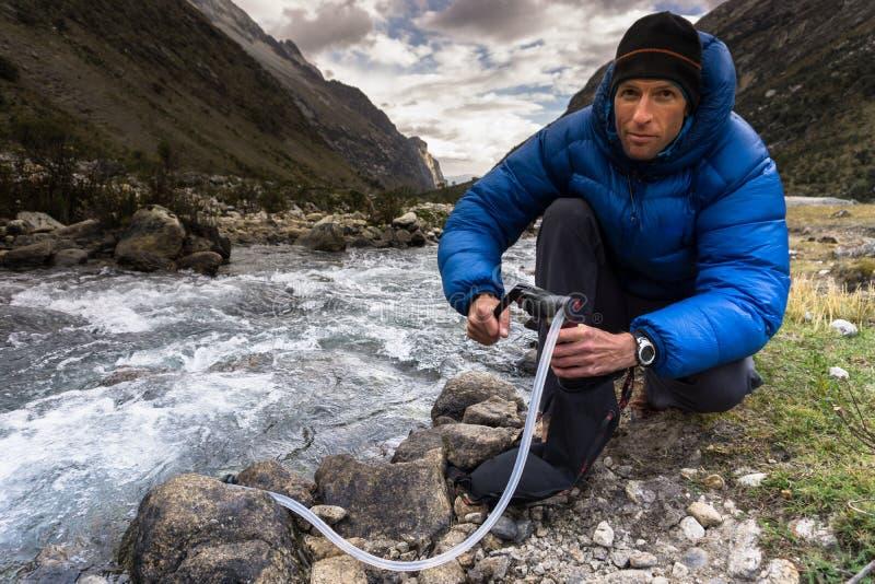 Hombre en agua potable de filtración abajo de la chaqueta azul de un río de la montaña en Perú fotos de archivo libres de regalías