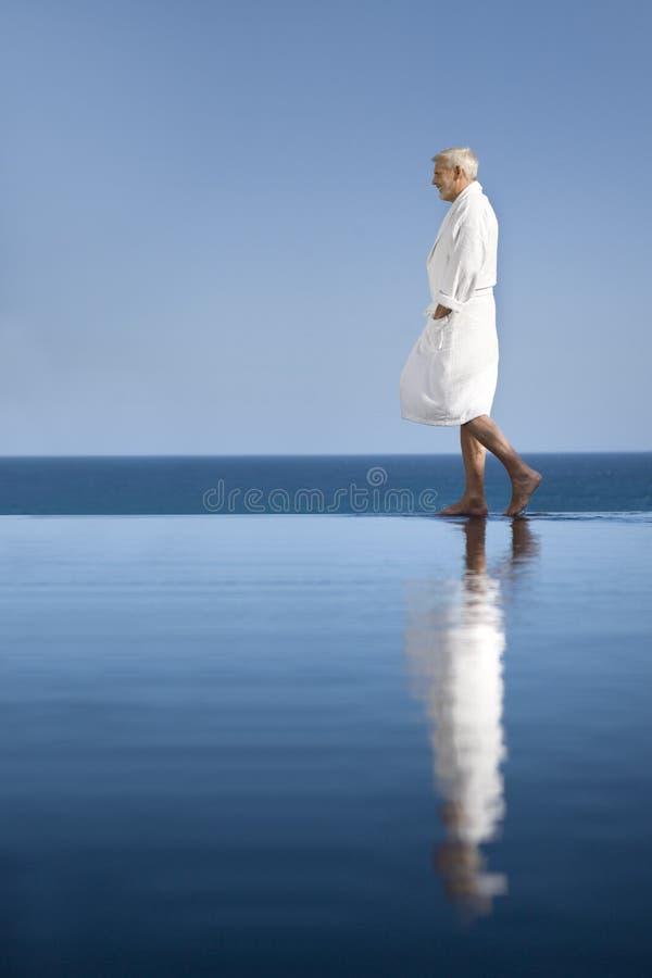Hombre en albornoz por la piscina imágenes de archivo libres de regalías