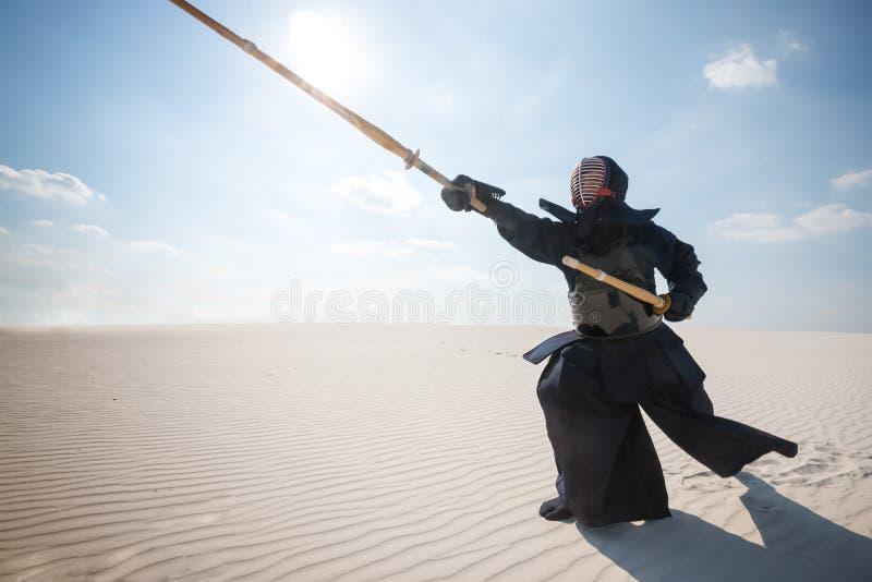 Hombre en armaduras japonesas tradicionales - el bogu, hace los wi profundos de una estocada fotos de archivo libres de regalías