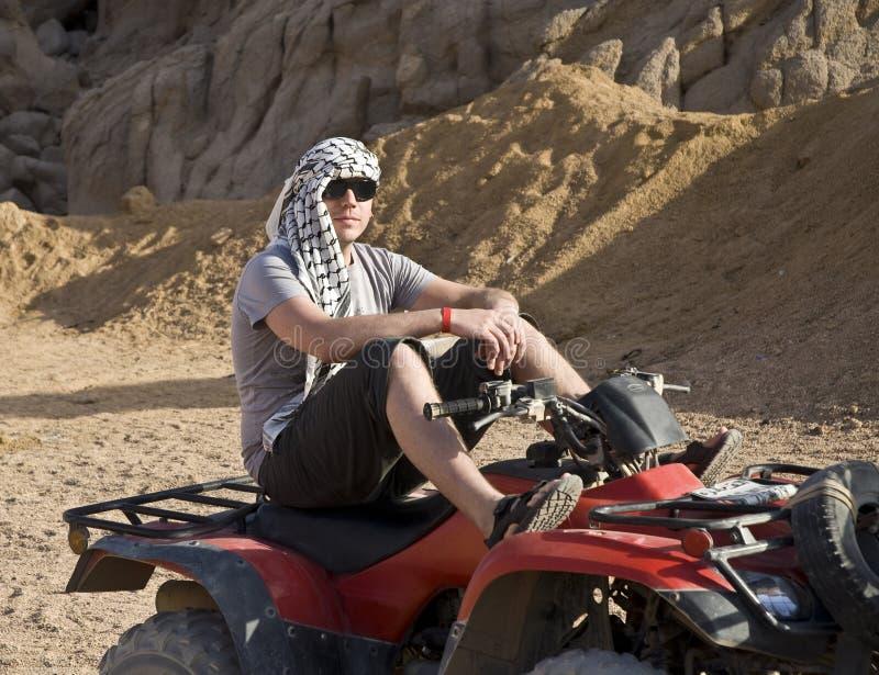 Hombre en ATV en desierto imagen de archivo