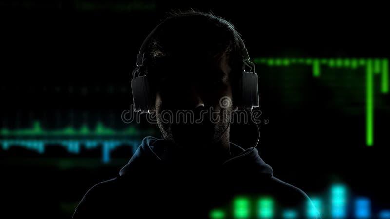 Hombre en auriculares en el fondo de los efectos del equalizador, nueva tecnología, cierre para arriba fotografía de archivo libre de regalías