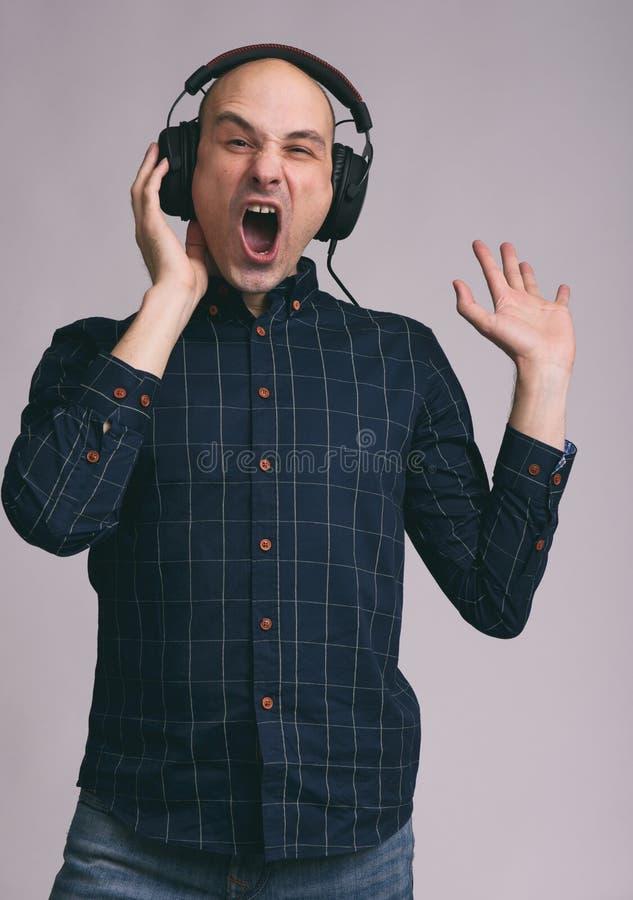 Hombre en auriculares que canta la canción fotos de archivo