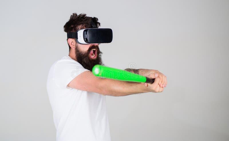 Hombre en béisbol del juego de las auriculares de la realidad virtual en gris Inconformista en las tecnologías modernas concentra foto de archivo
