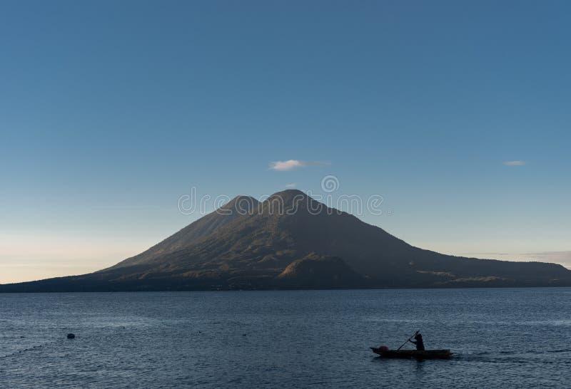 Hombre en barco y lago Atitlan en Guatemala Exposición larga Volcán en fondo Luz de la mañana fotos de archivo