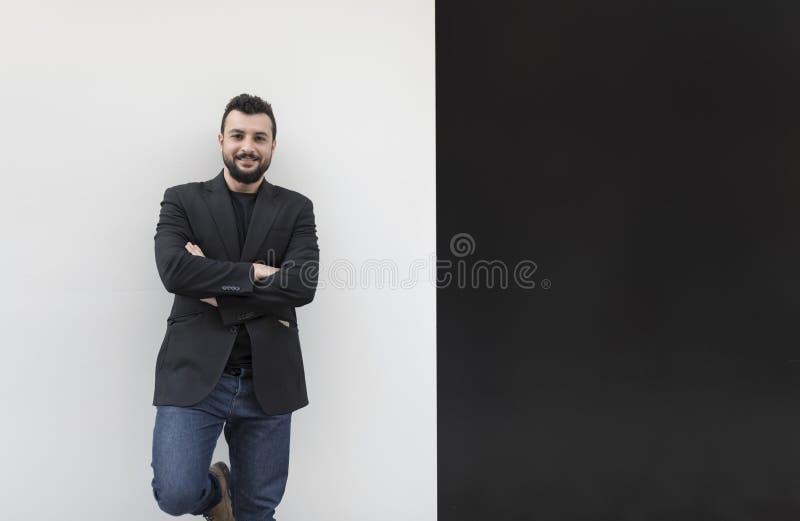 Hombre en blanco y negro en traje negro, con la barba negra y con los dientes imagen de archivo libre de regalías