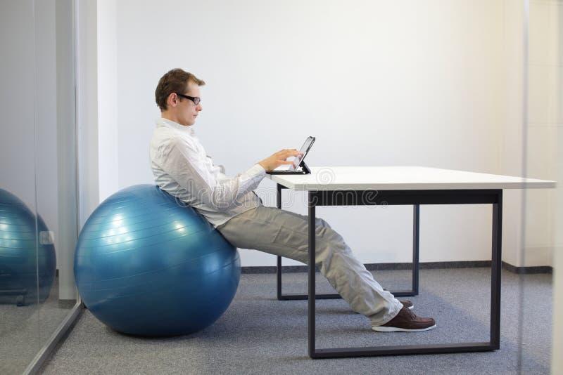 hombre en bola de la estabilidad en el escritorio imágenes de archivo libres de regalías