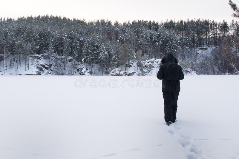 hombre en bosque durante tormenta de la nieve imagen de archivo