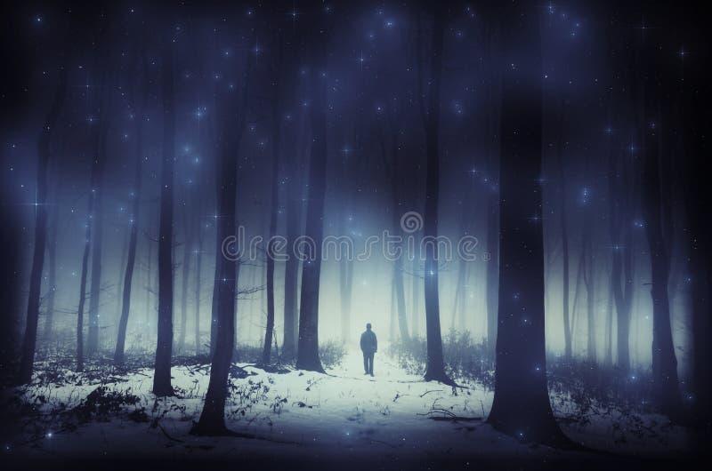 Hombre en bosque mágico surrealista en invierno con las estrellas fotos de archivo