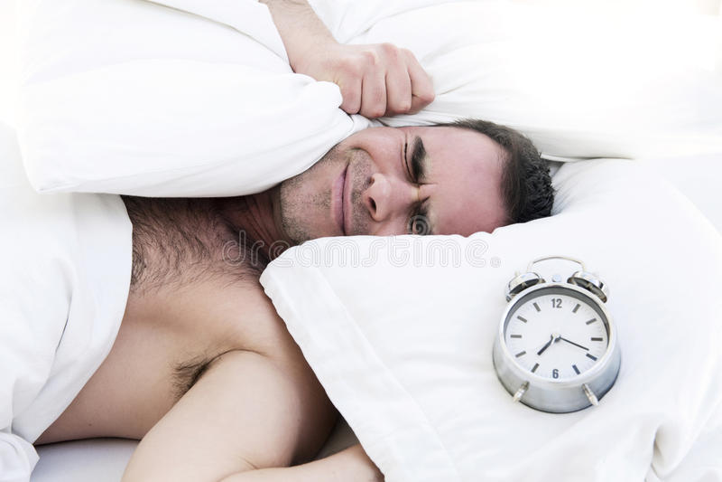 Hombre en cama con el despertador imágenes de archivo libres de regalías