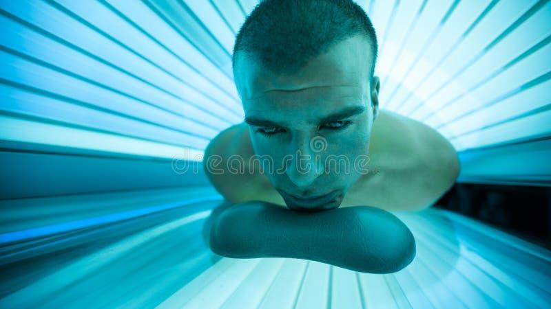 Hombre en cama que broncea en solarium imagenes de archivo