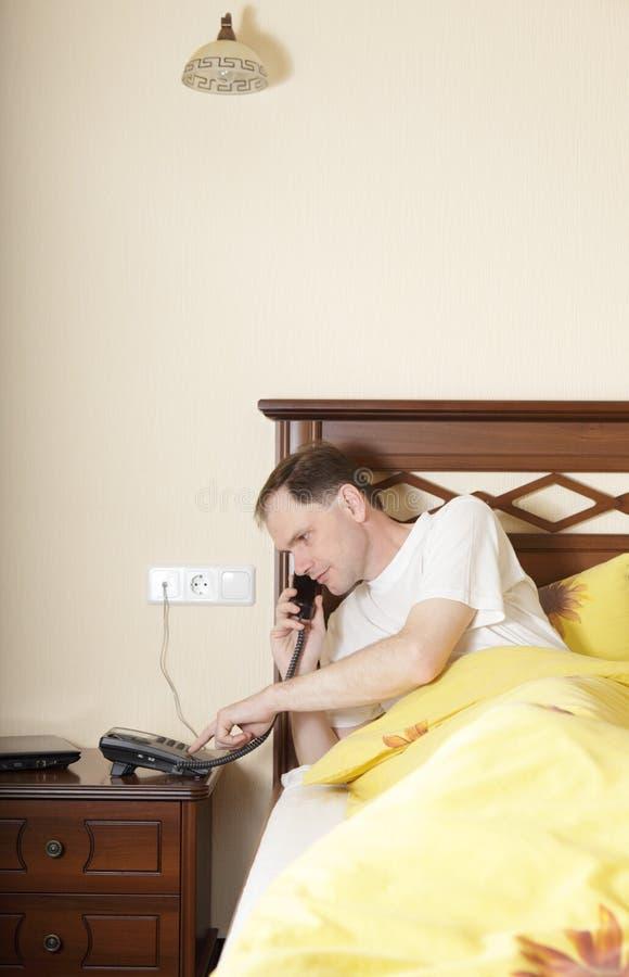 Hombre en cama que llama por el teléfono imagenes de archivo