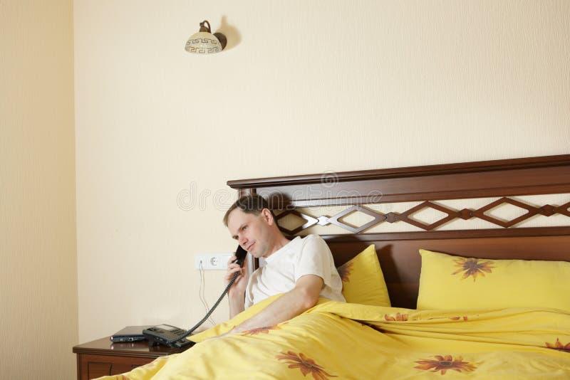 Hombre en cama que llama por el teléfono fotografía de archivo